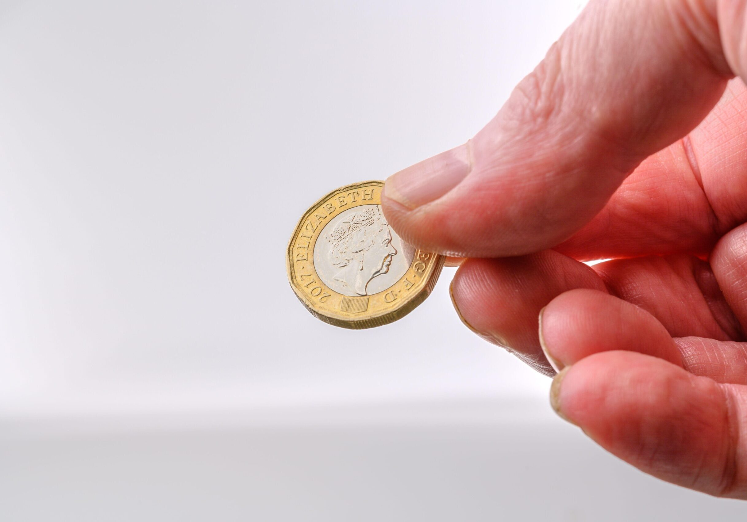 2BA8854 British Pound coin crown side in human hand for payment on white background with copy space